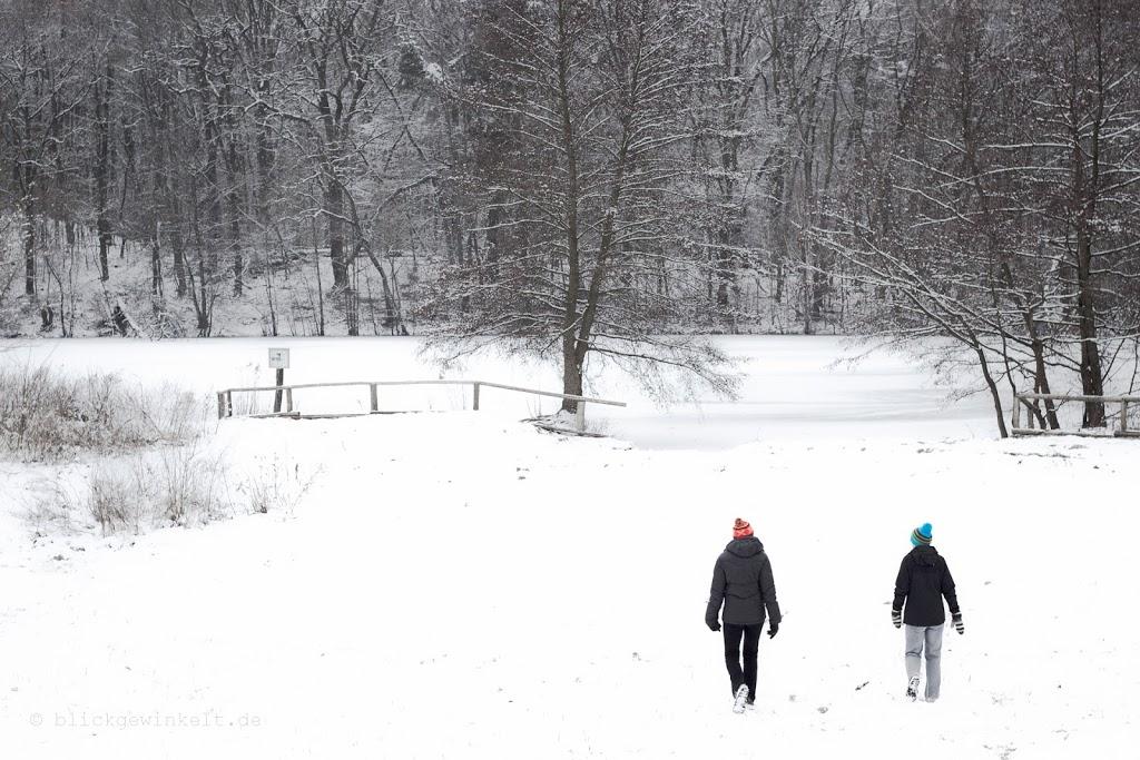 Winterlandschaft fotografieren: Feine Details betonen - zwei Spaziergänger im Schneewald mit bunten Mützen