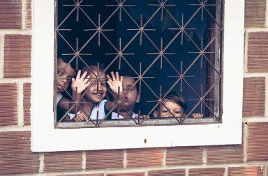 Kinder gucken aus vergittertem Fenster