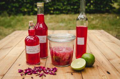 Rosenblütenwasser und Rosenblütensirup, Flaschen auf Holztisch