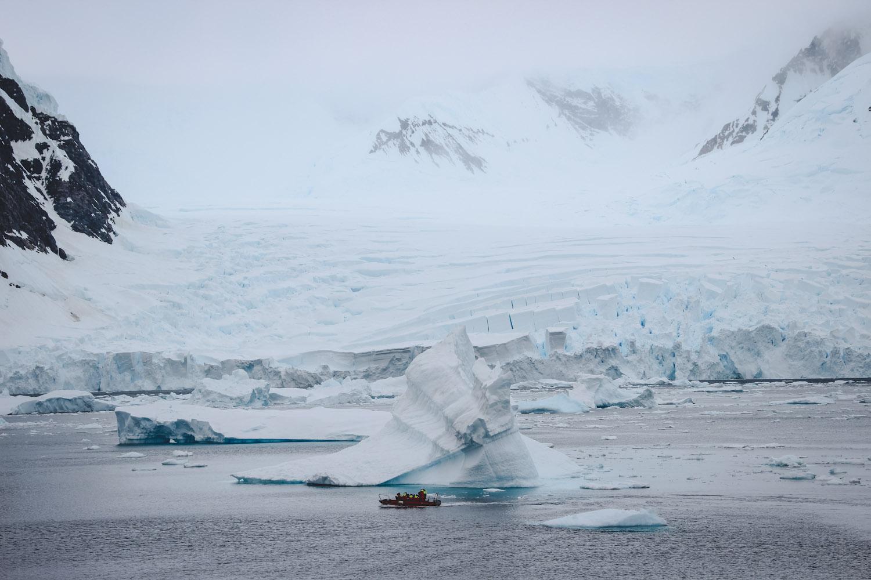 Zodiac in der Antarktis vor großem Eisberg und Antarktischem Festland
