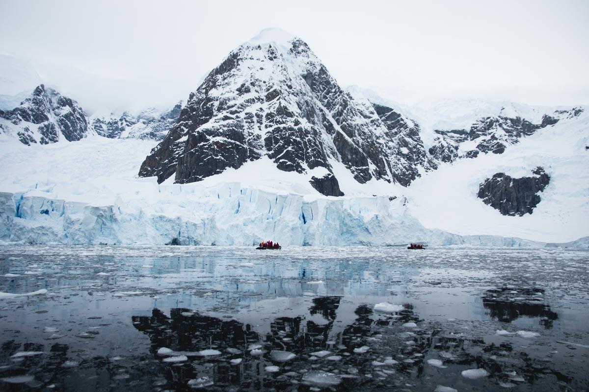 Winterlandschaft fotografieren: Berg in der Antarktis mit Wasserspiegelung und kleinem Schlauchboot