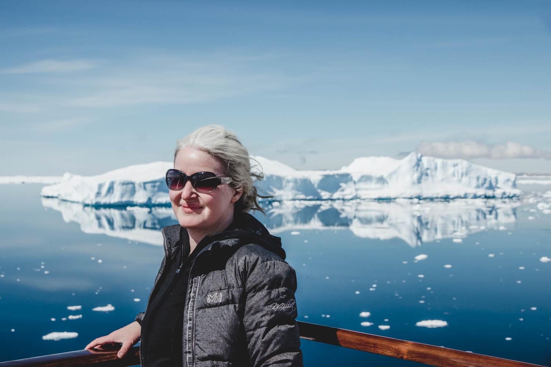 Inka auf Deck, im Wasser ein sich spiegelnder Eisberg