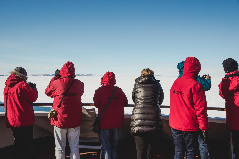 Gäste der MS Hanseatic stehen an Deck und schauen auf das Meereis in der Antarktis