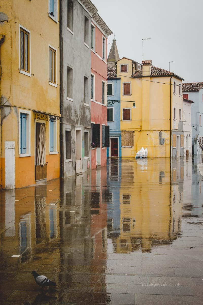 Burano: Spiegelnde Häuserfassaden auf dem regennassen Asphalt
