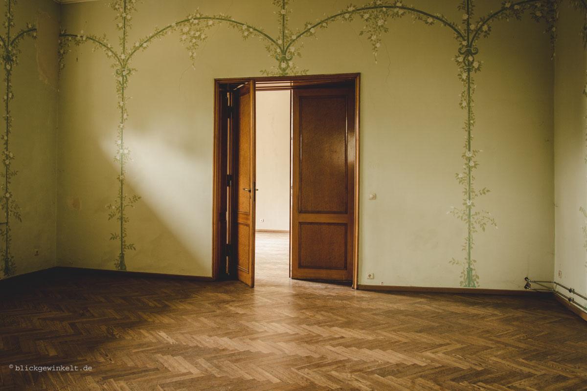 Verlassen: Leeres Zimmer mit Holztür und alter Tapete