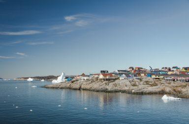 Bunte Häuser am Fjord mit Eisbergen