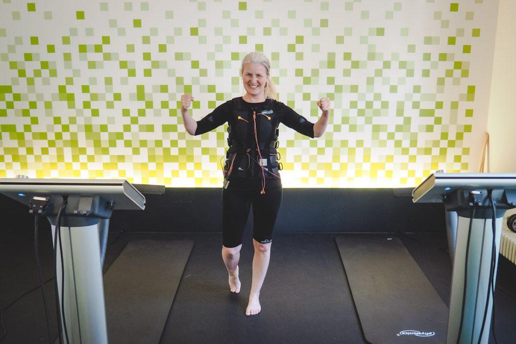 Frau trainiert mit Elektroden-Weste