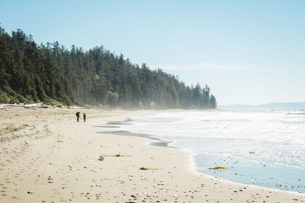 Strand mit Waldhintergrund und zwei Wanderern auf Vancouver Island