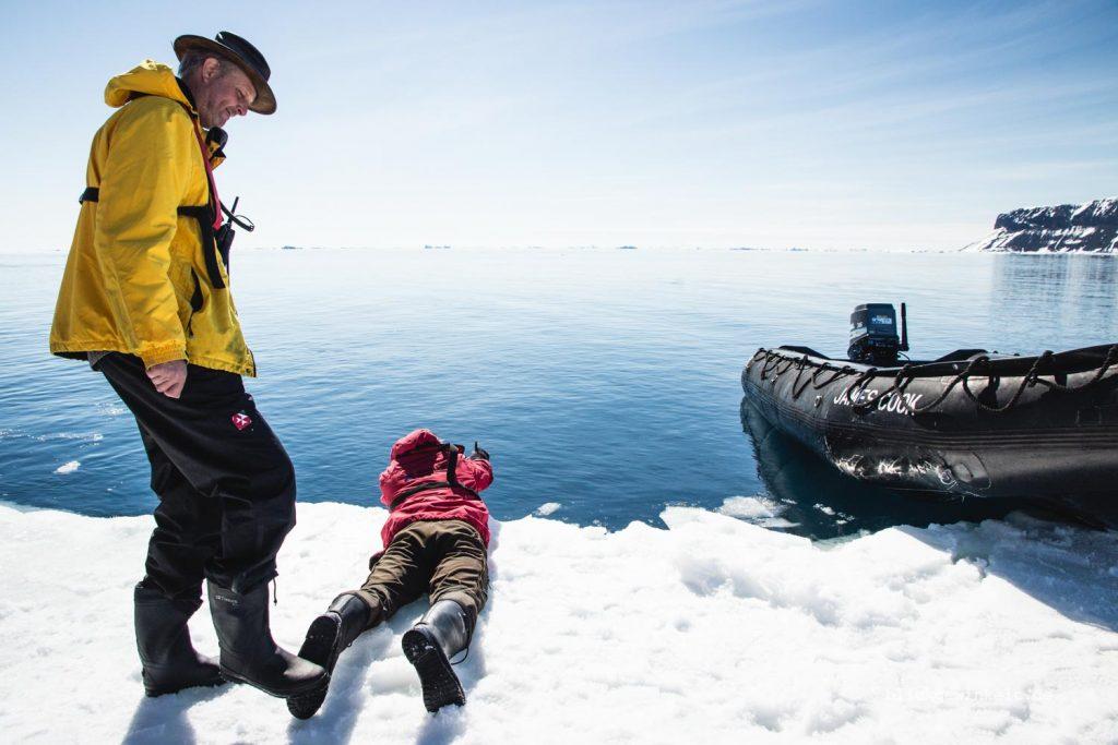 Mann filmt auf dem Bauch unter die Meereisgrenze