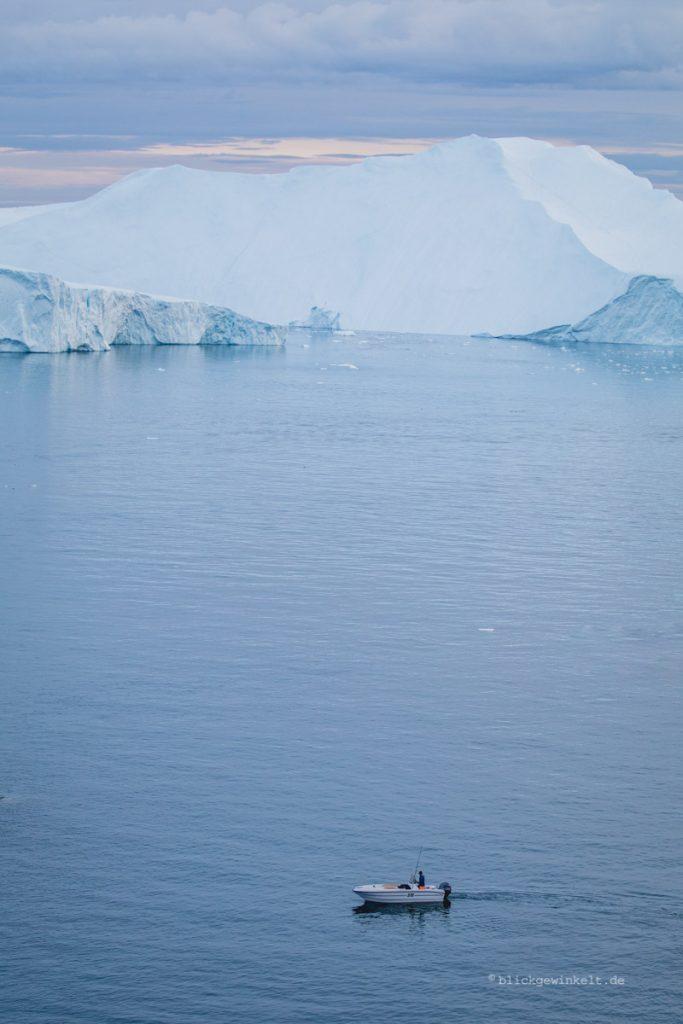 Fischer vor Eisberg in Grönland