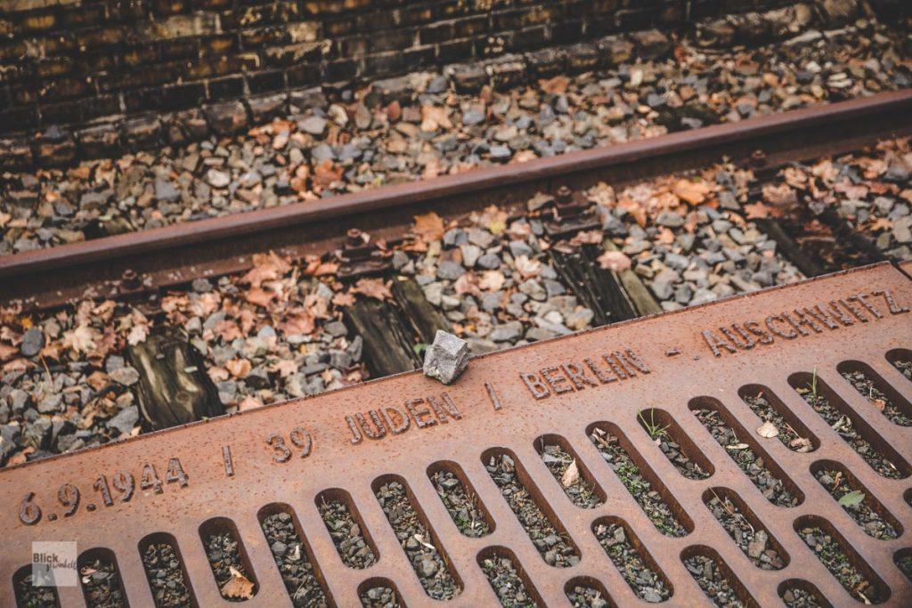 Gusseiserne Bahnsteigkante mit Gedenkinschrift an deportierte Juden.