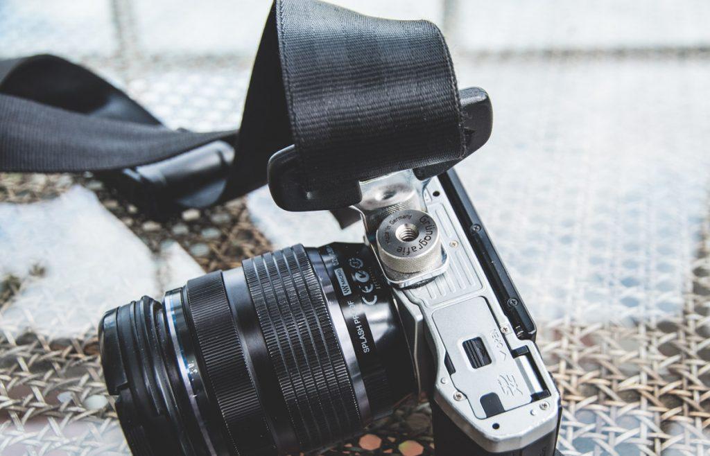 Mittels einer dicken Schraube wird der Tragegurt an der Kamera befestigt.