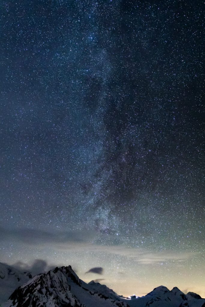 Milchstraße über schneebedeckten Bergen