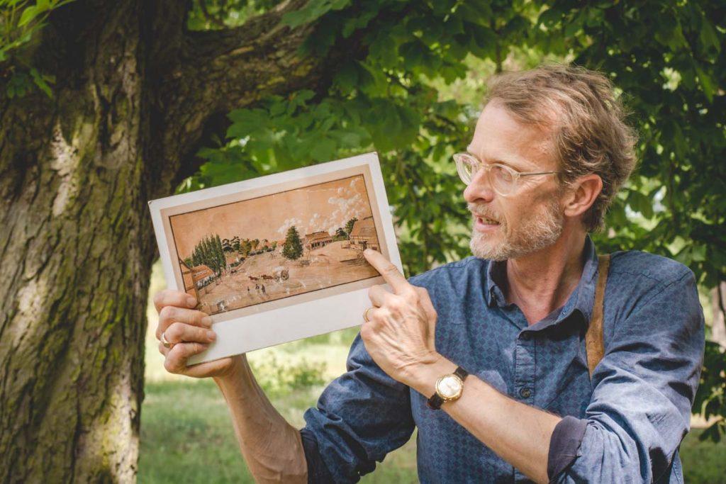 Museumsleiter zeigt alte Bilder