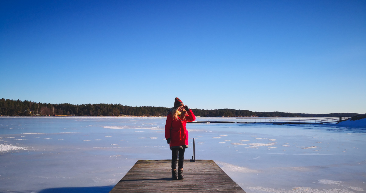 Südfinnland, Frau auf Steg am gefrorenen See