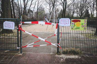 abgesperrter Spielplatz mit Warnschild Coronavirus
